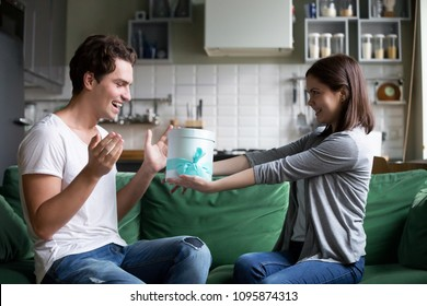 Smiling girl giving gift box to excited boyfriend making present for his birthday sitting on sofa at home together, loving wife congratulating happy husband presenting unexpected romantic surprise