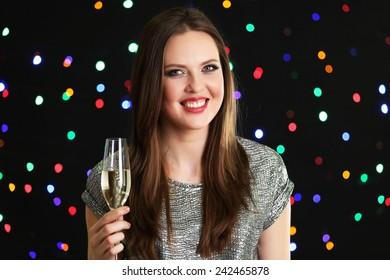 Smiling girl with glass of wine on lights background