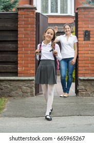 Smiling girl going out the house to school. Mother standing in doorway and waving to her