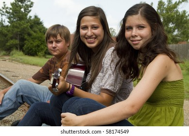 A smiling girl with a guitar sits outside on the railroad tracks with friends.