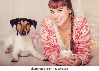 Smiling girl  and happy dog, having christmas snacks in christmas decorated living room
