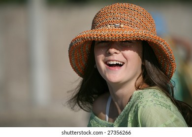 a smiling girl in hat a pleased smile upon one's face