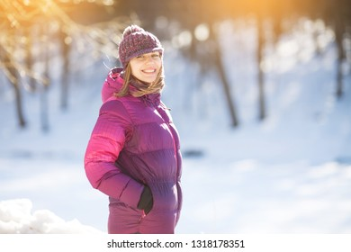 Smiling girl in a hat standing in the winter forest