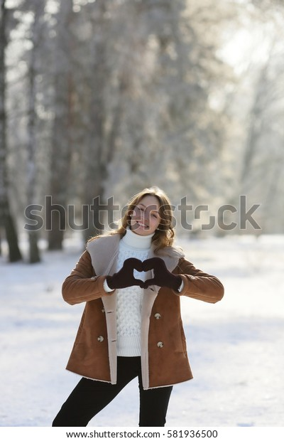 Smiling girl with heart from hands, on walk in winter park