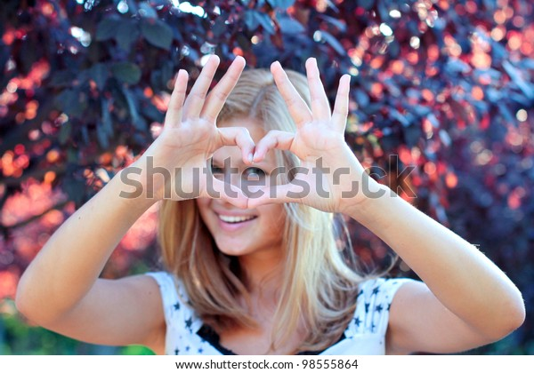 Smiling girl with heart sign