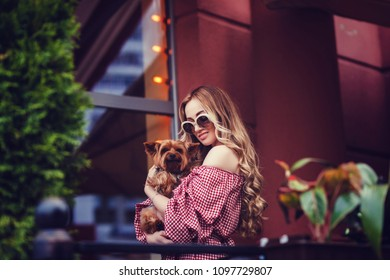 Smiling girl with her dog in summer city