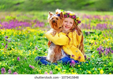 Smiling girl with her little dog sitting at the spring blooming  meadow