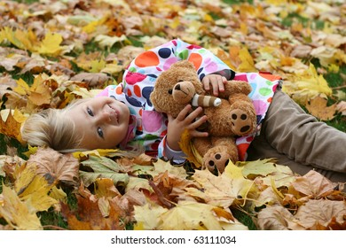 Smiling girl  with her teddy bear in autumn park