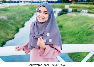 Smiling girl in hijab covering her eyes with happiness