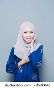 Smiling girl in hijab covering her eyes with happiness.Muslim Hijab Fashion Portraiture.