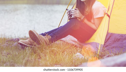 smiling girl hiker in a tent and holding a cup mountains in the background