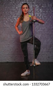 smiling girl holding a barbell in hand, great strength, full length