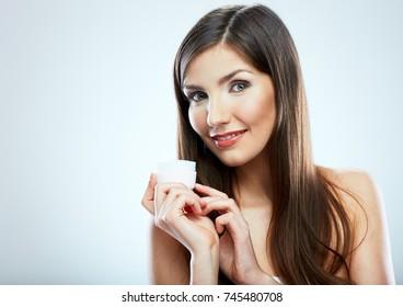 Smiling girl holding beauty skin care cream in glass jar. Isolated studio portrait.