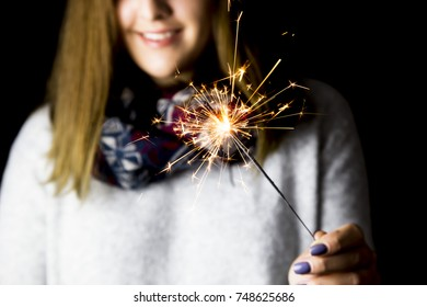 smiling girl holding a bengal fire on Christmas day. Close up