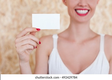 Smiling girl holding a blank business card in her hand with red nails. Concept of advertising and PR.