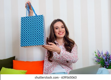 Smiling girl holding blue gift package with circle pattern. Female blogger shows how to make your surprise ideal.