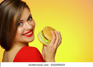 Smiling girl holding burger looks over shoulder. Isolated portrait. Yellow back.