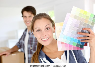 Smiling girl holding colour charts to decorate house