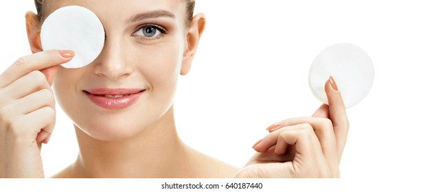 Smiling girl holding cotton pads up to her eyes. Close up portrait of beautiful girl on white background. Youth and skin care concept
