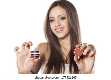 smiling girl holding a gambling chips in her nadds