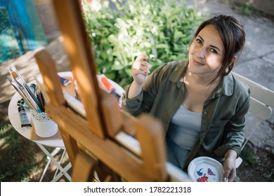 Smiling girl holding paintbrush and painting outdoor. Happy lady holding paintbrush and palette while sitting in garden art studio and looking at camera.
