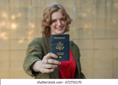 Smiling girl holding passport with arm extended towards camera