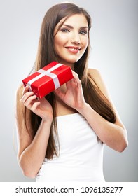 Smiling girl holding red gift box. Young woman with long hair beauty style portrait.