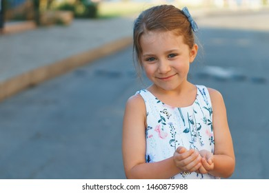 smiling girl holding something in hands in street