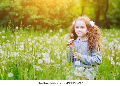 Smiling girl holding white dandelion in meadow. Healthy, breathing, medical, allergy, happy childhood concept.