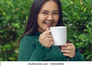 smiling girl holding a white mug