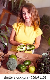 Smiling girl holds cutted green pepper at the table full of natural food, healthy food concept