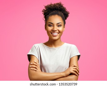 Smiling girl holds hands crossed. Photo of african american girl wears casual outfit on pink background. Emotions and pleasant feelings concept.