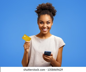 Smiling girl holds smart phone and credit card. Photo of african american girl wears casual outfit on blue background. Emotions and pleasant feelings concept.