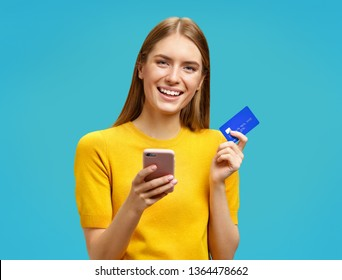 Smiling girl holds smartphone and credit card. Photo of beautiful girl in yellow sweater on blue background. Emotions and pleasant feelings concept.
