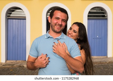 Smiling girl hugging her boyfriend in front of the yellow house with blue door