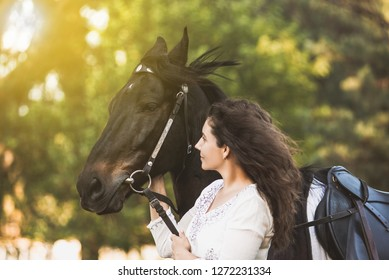Smiling girl hugs her horse pet