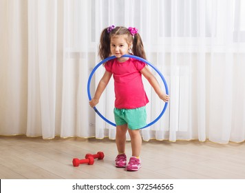 smiling girl with hula hoop at home