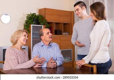 Smiling girl introducing her boyfriend to her happy parents indoor
