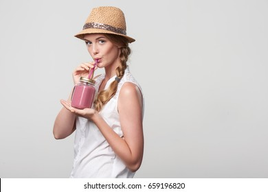 Smiling girl with jar tumbler mug drinking through straw a pink smoothie drink, portrait over grey background with blank copy space