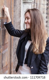 Smiling girl knocks on the closed door of the church