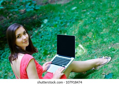 Smiling girl with a laptop at the park