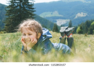 smiling girl laying in grass and holding hands at face