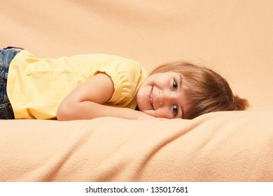 The smiling girl lies on a sofa