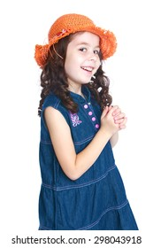 Smiling girl with long black hair wearing an orange hat and long black denim dress is photographed turning to the camera sideways