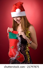 Smiling girl looking into Christmas stocking over red background