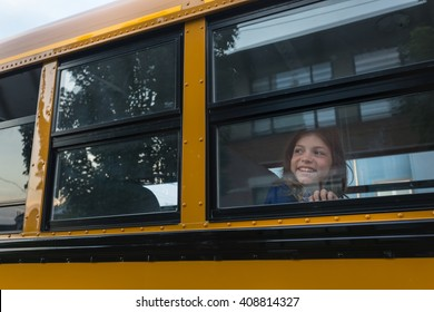 Smiling girl looking out school bus window