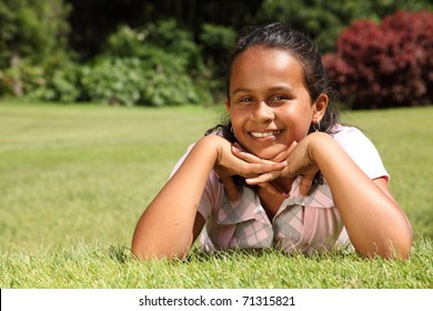 Smiling girl lying on grass chin on hands