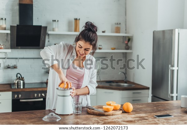 smiling girl making fresh orange juice with juicer at wooden table in kitchen