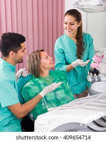 Smiling girl and male dentist with his assistant during check up at dental clinic