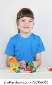 Smiling girl molds toys from plasticine on white table in white room